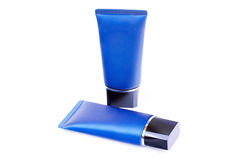 Tubos azules con la crema aislada en blanco Fotos de archivo libres de regalías