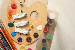 Tubos com pinturas da cor do artista profissional e da paleta na tabela, vista superior fotos de stock royalty free
