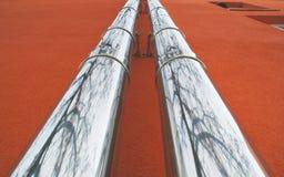 Tubos de acero en una pared roja Foto de archivo