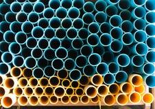 Tubos de agua azules y amarillos del PVC en el almacén Fotografía de archivo