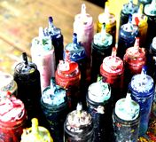 Tubos de color del foco con una pintura en un fondo de la tabla foto de archivo libre de regalías