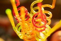 Tubos de cor para sucos bebendo em um fundo da cor O fundo brilhante borrado transmite a atmosfera festiva foto de stock royalty free