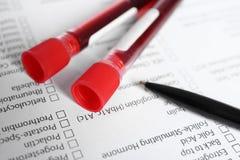 Tubos de ensaio com as amostras de sangue para a análise no formulário da análise laboratorial imagens de stock royalty free