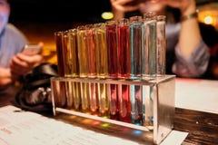 Tubos de ensaio com líquido multi-colorido Álcool em uns tubos de ensaio na barra escura imagem de stock royalty free