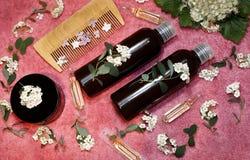 Tubos de ensaio com os cosméticos em flores frescas Fotos de Stock Royalty Free