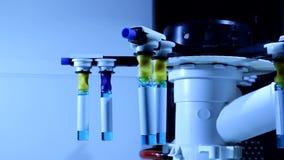 Tubos de ensaio da rotação com líquido químico azul no equipamento da pesquisa video estoque