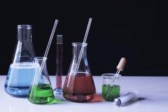 Tubos de ensaio químicos do laboratório de vidro com líquido para analítico, médico, farmacêutico e a pesquisa científica imagens de stock