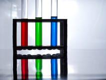 Tubos de ensayo con el líquido azul, verde y rojo en un estante para los tubos de ensayo en una tabla blanca y un fondo blanco fotografía de archivo
