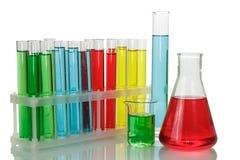 Tubos de ensayo con los líquidos coloridos en un estante, un frasco químico y un b fotos de archivo libres de regalías