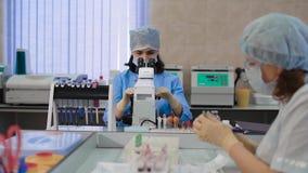 Tubos de ensayo de la sangre que son analizados e intercambiados por un técnico de laboratorio Trabaje en el laboratorio médico e almacen de video