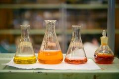 Tubos de ensayo y frascos del laboratorio con el líquido del color imagenes de archivo