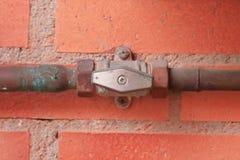 Tubos de gas y una válvula contra una pared de ladrillo roja fotografía de archivo libre de regalías
