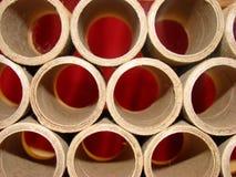 Tubos de la cartulina con el fondo rojo imagenes de archivo