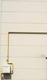 Tubos de Yelow y metro de gas en la pared gris Foto de archivo