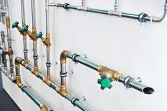 Tubos del abastecimiento de agua del metal con las válvulas Foto de archivo libre de regalías