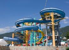 Tubos, diapositivas y piscina coloridos en el aquapark Foto de archivo