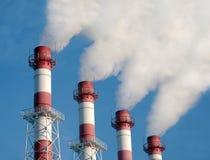Tubos industriales con el humo blanco sobre el cielo azul, vista lateral Imagen de archivo