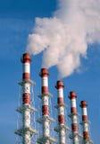 Tubos industriales con el humo blanco sobre el cielo azul, vista lateral Fotografía de archivo