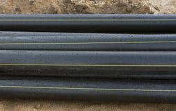 Tubos negros del pvc en la arena Foto de archivo
