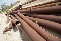 Tubos oxidados dejados en campo Imagen de archivo