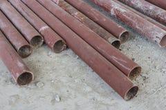 Tubos para la construcción que miente en la tierra concreta Fotografía de archivo