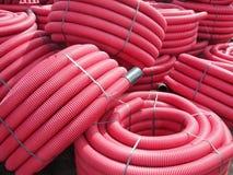 Tubos plásticos acanalados rojos usados para las líneas eléctricas subterráneos Foto de archivo