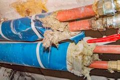 Tubos viejos de la fontanería del agua de enfriamiento de la calefacción con las válvulas fotografía de archivo libre de regalías