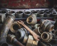 Tubos viejos oxidados del fontanero con la llave y la caja de herramientas oxidadas foto de archivo libre de regalías