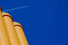 Tubulação amarela com plano no céu azul Fotos de Stock