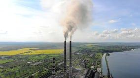 Tubulação da vista aérea teleplastic que se emite o fumo preto, no fundo da natureza bonita, de campos verdes e de um grande lago filme