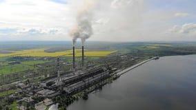 Tubulação da vista aérea teleplastic que se emite o fumo preto, no fundo da natureza bonita, de campos verdes e de um grande lago video estoque