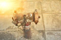 A tubulação de água velha oxidada do metal no público sob a luz solar e Imagem de Stock Royalty Free