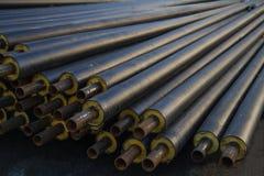 Tubulação de aço preta com isolação térmica no canteiro de obras em um envoltório plástico do tubo que encontra-se no pavimento u Imagens de Stock