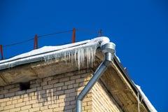 A tubulação de dreno e os sincelos na borda do telhado da construção fotografia de stock
