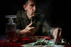 Tubulação do fumo do homem e pôquer do jogo fotografia de stock royalty free