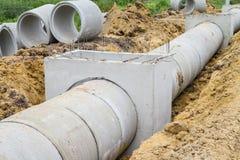 Tubulação e câmara de visita concretas da drenagem sob a construção Imagens de Stock