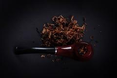 Tubulação e cigarro no fundo preto Foto de Stock