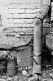 A tubulação e a parede de tijolo sujas na jarda foto de stock royalty free