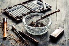 Tubulação fina no cinzeiro de vidro com cigarros e isqueiro Fotos de Stock Royalty Free