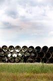 Tubulação longa empilhada ao lado da estrada Fotografia de Stock Royalty Free