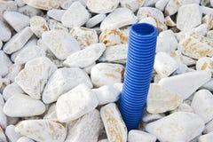 Tubulação ondulada azul para o cabo bonde que sai da terra fotos de stock royalty free