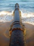 Tubulação oxidada na praia Fotos de Stock Royalty Free