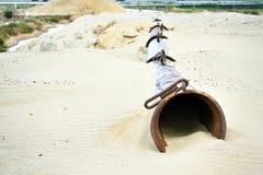 A tubulação seca da draga encontra-se na areia na pedreira da areia Fotografia de Stock