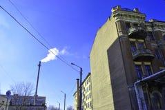 Tubulação velha com fumo, cantos residenciais das construções de tijolo com janelas e fios no fundo brilhante do céu azul do inve imagem de stock