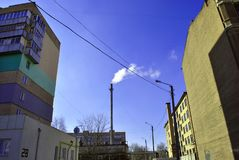 Tubulação velha com fumo, cantos residenciais das construções de tijolo com janelas e fios no fundo brilhante do céu azul do inve fotografia de stock royalty free