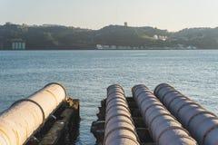Tubulações brancas industriais que alimentam no Tagus River, Lisboa, Portugal imagem de stock royalty free