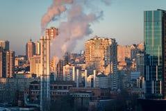 Tubulações da caldeira contra a cidade da noite Fotos de Stock Royalty Free