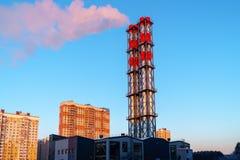 Tubulações da estação térmica com o fumo que vem deles contra o céu azul imagens de stock