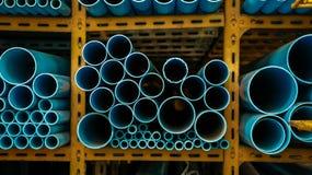Tubulações de água azul na cremalheira do metal amarelo - tamanhos diferentes foto de stock royalty free