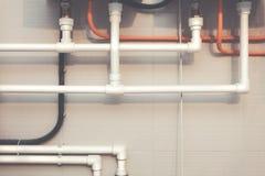 Tubulações de água plásticas brancas do sistema de encanamento com encaixe do Y-ramo, o tubo ondulado preto e a parede com azulej Fotografia de Stock Royalty Free